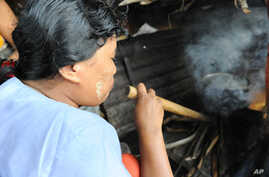 Fuel-efficient stoves use significantly less firewood than a traditional three-stone stove. This woman in Myanmar is using a pipe to help increase the fire's flames to cook the food.