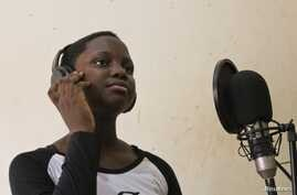 Rapper MC Loy, 13, records rap news to appeal to a younger audience, Kampala, March 20, 2014. (Hilary Heuler/VOA)