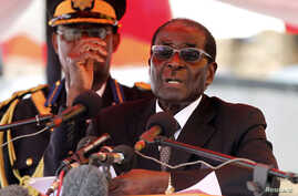 Zimbabwean President Robert Mugabe gestures as he addresses mourners gathered for the burial of Vice-President John Nkomo at National Heroes Acre, in Harare, Zimbabwe, January 21, 2013.