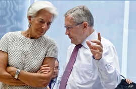 Managing Director of the International Monetary Fund Christine Lagarde, left, speaks with Klaus Regling, chair of the European Financial Stability Facility, during a meeting of eurozone finance ministers at the EU Lex building in Brussels, July 11, 2