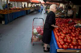"""A elderly woman buys goods at a vegetable market in Athens, on Friday, July 3, 2015. The brief but intense campaign in Greece's critical bailout referendum ends Friday, with simultaneous rallies in Athens for """"Yes"""" and """"No"""" supporters in what an opin"""
