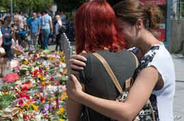 People mourn beside the Olympia shopping center where a shooting took place leaving nine people dead two days ago in Munich, Germany, Sunday, July 24, 2016.
