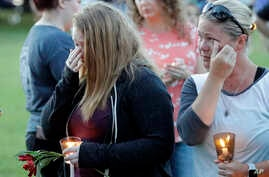 Santa Fe High School freshman Kylie Trochesset, left, and her mother, Ashlee, wipe away tears during a prayer vigil following a shooting at Santa Fe High School in Santa Fe, Texas, May 18, 2018.