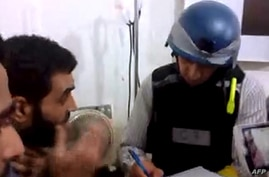An image grab taken from a video posted by Syrian activists on Aug. 26, 2013 allegdly shows a UN inspector (R) listening to the testimony of a man in the Damascus subburb of Moadamiyet al-Sham.