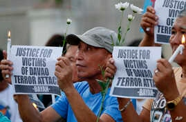 FILE -  Protesters display placards during a prayer vigil in Manila, Philippines, for the victims of an explosion in Davao City, Philippines, Sept. 3, 2016. Suspected Abu Sayyaf extremists detonated a bomb at the night market in Davao City, killing a
