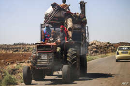 A Syrian family rides with belongings on a tractor-drawn trailer as they flee from fighting in the southern Syrian province of Daraa on June 21, 2018.