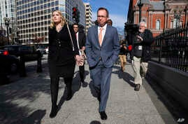 Mick Mulvaney, center, walks to the Eisenhower Executive Office Building after leaving the Consumer Financial Protection Bureau in Washington, Nov. 27, 2017.