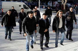 FILE - Four Turkish military officers in suits wearing handcuffs, center, escorted by Greek plainclothes police officers, arrive at the Supreme Court in Athens, Jan. 13, 2017.