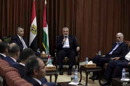 Head of the Hamas political bureau, Ismail Haniyeh, center, and Hamas leader in the Gaza Strip Yahya Sinwar, right, meet with Egypt's general intelligence chief, Khaled Fawzy, and others in Haniyeh's office in Gaza City, ahead of talks in Cairo, Oct.
