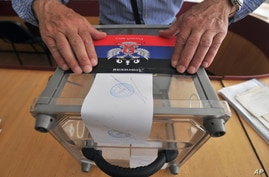 """Member of the regional election commission glues sticker depicting flag of the self-proclaimed """"Donetsk People's Republic"""" atop Ukraine's state emblem as he prepares ballot boxes, Donetsk, eastern Ukraine, May 10, 2014."""