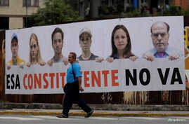 """A man walks past a banner which reads """"The Constituent Assembly will not happen,"""" in Caracas, Venezuela, July 24, 2017. Pictured on the banner are Henrique Capriles (left), Venezuelan opposition leader and Governor of Miranda state, Lilian Tintori (2"""