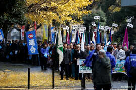 Protesters demanding return of disputed islands claimed by both Japan and Russia, called the Northern Territories in Japan and the Southern Kuriles in Russia, march under ginkgo trees in Tokyo, Dec. 1, 2016. Russian President Vladimir Putin will begi