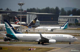 A SilkAir Boeing 737 Max 8 plane (behind) sits on the tarmac near a hangar after suspended operations for all Boeing 737 Max 8 planes, at Changi Airport in Singapore, March 12, 2018.