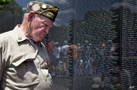 World War II Army veteran Jimmy Bishop, Jr., 87, of Old Bridge, N.J., reacts as he looks at the names on the Vietnam Veterans Memorial for the first time on Sunday, May 25, 2014.