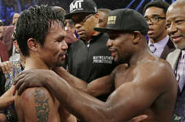 Manny Pacquiao, from the Philippines (L), and Floyd Mayweather Jr., embrace in the ring at the finish of their welterweight title fight in Las Vegas, May 2, 2015.