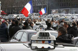 Striking French taxi drivers attend a national protest about competition from private car ride firms like Uber, in Paris, Jan. 26, 2016.