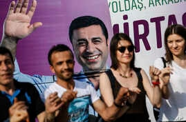 FILE - People dance in front of an election campaign poster of Selahattin Demirtas, a jailed pro-Kurdish politician and presidential candidate in Turkey's snap presidental poll, in Istanbul, June 5, 2018.