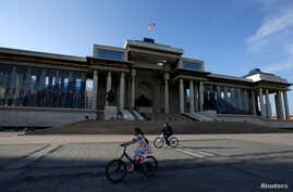 FILE - People cycle past the parliament building at Genghis Square in Ulaanbaatar, Mongolia, June 27, 2016.