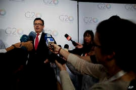 Reporters surround Spanish Economy, Industry and Competitiveness Minister Roman Escolano as he speaks on the sidelines of the G-20 finance ministers and central bankers summit in Buenos Aires, Argentina, March 20, 2018.