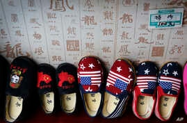 FILE - Chinese-made children shoes carrying a Chinese map and U.S. flags are on display for a sale at a shop in Beijing, July 13, 2018.
