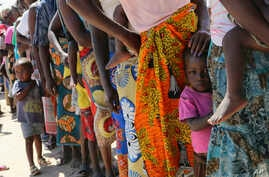 Women and children wait in a queue for oral cholera vaccinations, at a camp for displaced survivors of cyclone Idai in Beira, Mozambique, Wednesday, April 3, 2019.