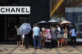 Mainland Chinese tourists wait outside a Chanel store at Hong Kong's Tsim Sha Tsui shopping district, Oct. 1, 2014, with part of it being blocked by protesters.