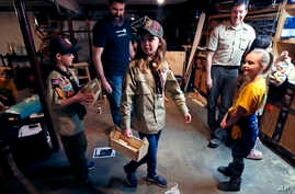 "FILE - Tatum Weir, center, carries a tool box she built as her twin brother Ian, left, follows after a Cub Scout meeting in Madbury, N.H., March 1, 2018. Fifteen communities in New Hampshire are part of an ""early adopter"" program to allow girls to be"