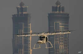 A Volocopter prototype flies in front of the two hotel towers during a test flight of pilotless taxis in Dubai, United Arab Emirates, Sept. 26, 2017.