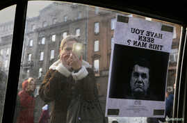 """A woman takes a photo of a """"Wanted"""" notice for fugitive Ukrainian president Viktor Yanukovich, plastered on the window of a car near Kyiv's Independence Square Feb. 24, 2014."""