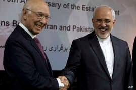 Iranian Foreign Minister Mohammad Javad Zarif, right, shakes hands with former Pakistan's adviser on foreign affairs Sartaj Aziz in Islamabad, Pakistan, March 12, 2018.