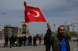 A supporter of Turkey's main opposition Republican People's Party, CHP, waves a national flag as people gather for a sit-in protest in central Istanbul's Taksim Square, Monday, April 16, 2018.