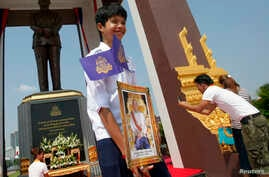A student holds a portrait of Cambodia's King Norodom Sihamoni (C), after the unveiling ceremony of a statue (back) of the late King Norodom Sihanouk in central Phnom Penh, Oct. 11, 2013.