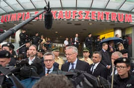 German Interior Minister Thomas de Maiziere, left, and Bavaria's Interior Minister Joachim Herrmann, right, give a media conference in front of the Olympia shopping center where a shooting took place leaving nine people dead the day before in Munich,