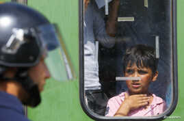 A migrant boy looks at a Hungarian policeman at the railway station in the town of Bicske, Hungary, Sept. 3, 2015.
