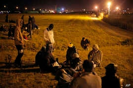 Migrants wait next to the Eurotunnel area as they attempt to access the Channel Tunnel, in Calais, northern France, Wednesday, July 29, 2015.