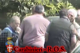 FILE - In this photo taken from a video provided by the Italian Carabinieri [paramilitary police], people identified by police as Italian cryme sindicate 'Ndrangheta' members kiss each other.