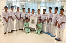 """The 12-member """"Wild Boars"""" soccer team and their coach rescued from a flooded cave pose with a drawing picture of Samarn Kunan, a former Thai navy diver who died working to rescue them at the Chiang Rai Prachanukroh Hospital, in Chiang Rai, Thailand,"""