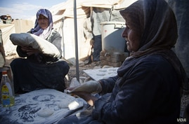 Syrian refugees make bread in a makeshift bakery between two tents in the Za'tari refugee camp, Jordan, November 15, 2012. (Y. Weeks/VOA)