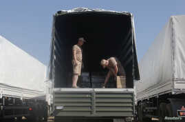 Drivers of a Russian convoy of trucks carrying humanitarian aid for Ukraine show the contents of their truck at a camp near Kamensk-Shakhtinsky, Rostov Region, Aug. 15, 2014.