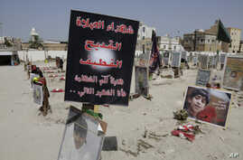 FILE - Religious flags, photographs and tributes to 21 victims of a suicide bombing of a Shi'ite mosque are displayed at a cemetery in al-Qudeeh, Saudi Arabia, May 30, 2015.