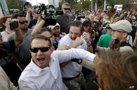 Two supporters of white nationalist Richard Spencer clash with a crowd of protesters after Spencer spoke at the University of Florida in Gainesville, Oct. 19, 2017.