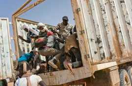 Migrants climb into a truck to head north into Algeria at the Assamaka border post in northern Niger on June 3, 2018.