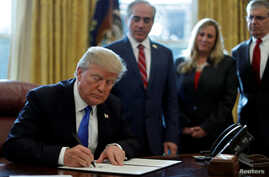 "U.S. President Donald Trump signs an Executive Order on ""Supporting our Veterans during their Transition from Uniformed Service to Civilian Life"" in the Oval Office of the White House in Washington, Jan. 9, 2018."