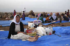 FILE - In this Sunday, Aug. 10, 2014 file photo, displaced Iraqis from the Yazidi community settle at a camp at Derike, Syria.