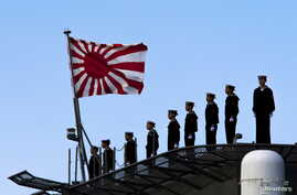FILE - Sailors stand on the deck of the Izumo warship as it departs from the harbour of the Japan United Marine shipyard in Yokohama, south of Tokyo.
