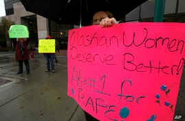 FILE - Eva Stassen tries to keep out of the rain as she joins other to protest the bail conditions of Anthony Rollins, an Anchorage Police Department veteran who was charged with multiple counts of sexual assault, outside Anchorage, Alaska courthouse...