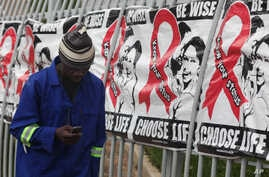 FILE - A man talks on a mobile phone as he walks past World AIDS Day banners in Johannesburg, South Africa, Dec. 1, 2014.