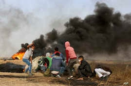 Palestinian protesters take cover during clashes with Israeli troops along Gaza's border with Israel, east of Khan Younis, Gaza Strip, April 5, 2018. A new round of protests along the border is expected Friday.