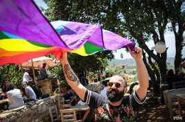 A man unfurls the rainbow flag at a small event held by Beirut Pride on Sunday, May 21, 2017. (J. Owens/VOA)