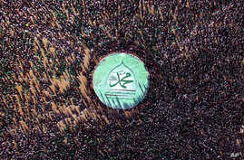 """Shiite rebels, known as Houthis, stand around a large banner with Arabic writing that reads,""""Muhammed"""" during the celebration of Moulid Al-Nabi, the birth of Islam's Prophet Muhammad in Sanaa, Yemen, Wednesday, Dec. 23, 2015."""